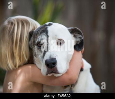 Portrait of sad looking dog hugged by three year old boy - Stock Photo