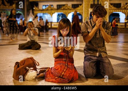 A young couple praying at Shwedagon Pagoda in Yangon, Myanmar Burma - Stock Photo