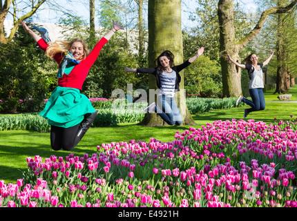 Three girls jumping above flowers field - Stock Photo