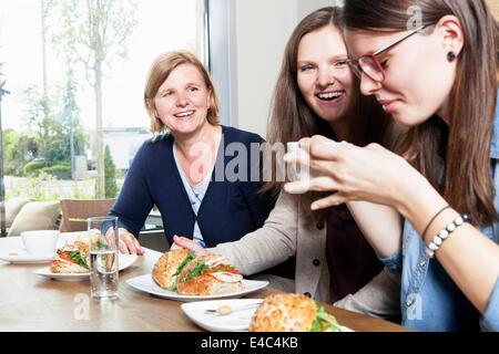 Three women having breakfast in a cafe - Stock Photo