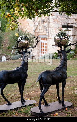 A pair of bronze stags with silver balls between their antlers in garden under an apple tree. - Stock Photo