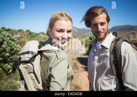 Hiking couple walking on mountain terrain smiling at camera - Stock Photo
