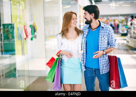 Portrait of happy young couple interacting while shopping in the mall - Stock Photo