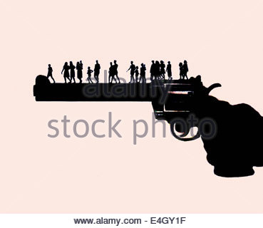 Large hand holding gun with people walking along barrel - Stock Photo