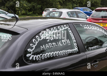 Window of honeymooners' black car painted with 'Just Married!!' - Stock Photo