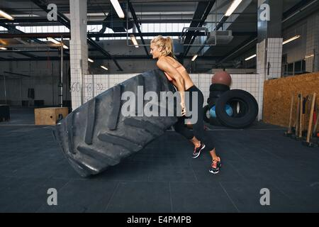 Fit female athlete flipping a huge tire. Muscular young woman doing crossfit exercise at gym. - Stock Photo