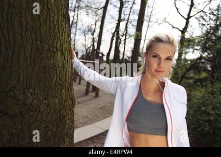 Pretty young woman standing by a tree at park. Attractive fitness female resting after outdoors training. - Stock Photo