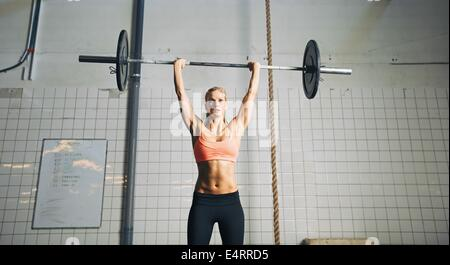 Muscular young female athlete doing weightlifting at crossfit gym. Fit young woman model lifting heavy weights at - Stock Photo
