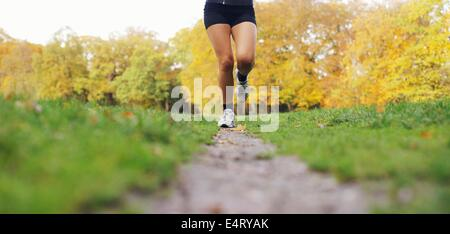 Low section image of young woman's legs running in park. Female athlete jogging in a park on a summer day. - Stock Photo