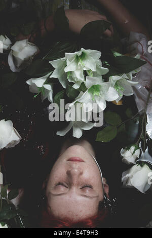 Innocence, Teen submerged in water with white roses, romance scene - Stock Photo