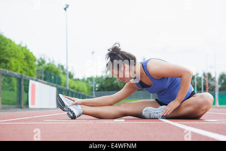 Woman stretching in a stadium - Stock Photo