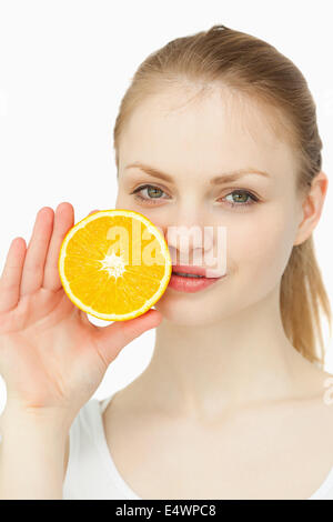 Woman placing an orange on her lips - Stock Photo