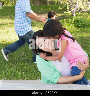 A mother in the park with her daughter, laughing and kissing each other. Father and son running on the grass. - Stock Photo