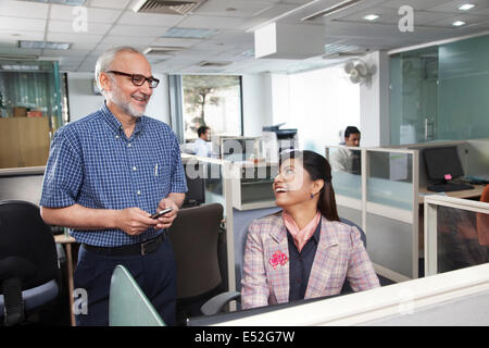 Senior man and woman having a chat in office - Stock Photo