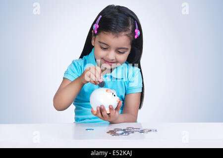 Smiling girl putting coins in piggy bank against blue background - Stock Photo
