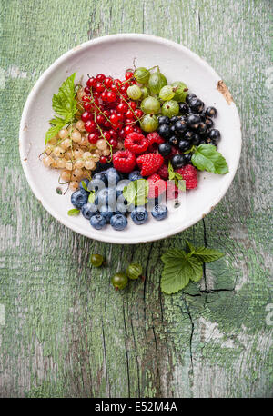 Mix of fresh berries with leaves in vintage ceramic colander on green rustic wooden background - Stock Photo