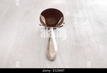 Antique spoon filled with chocolate. Chocolate dripping on white wood surface. Bright, clean setting. - Stock Photo