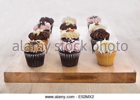 Assorted dozen cupcakes on wooden cutting board. Light wood, bright setting. - Stock Photo