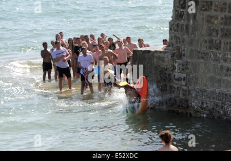 Brighton, Sussex, UK. 18th July, 2014. A young man leaps from a groyne on Brighton beach in a kayak as the hot weather - Stock Photo