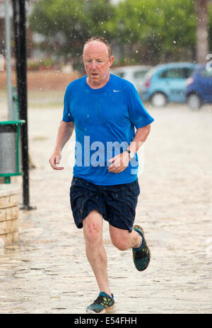 A man running through torrential rain and hail from a thunderstorm in Sivota, Greece. - Stock Photo