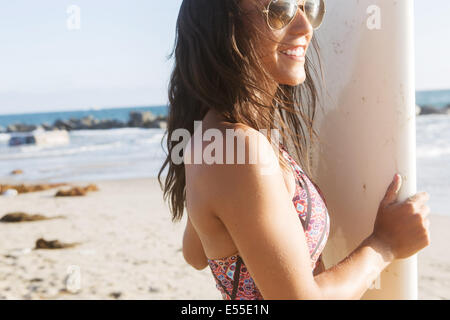 Young female surfer with sunglasses smiling while holding surfboard at the beach - Stock Photo