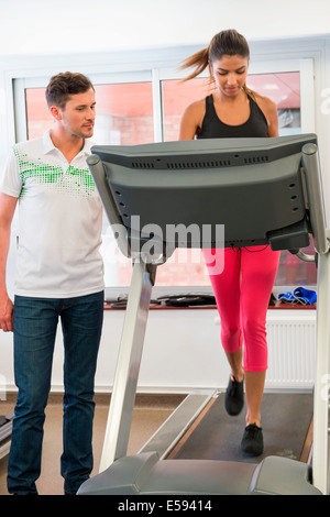 Instructor teaching a woman on a treadmill in a gym - Stock Photo