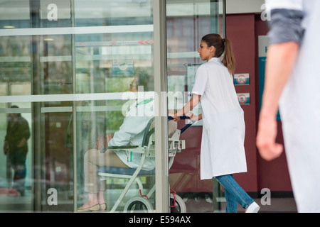 Female doctor pushing a patient sitting in a chair - Stock Photo