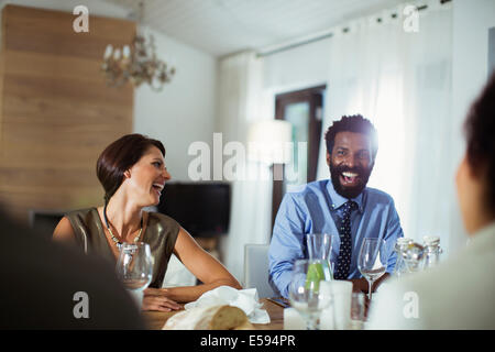 Friends laughing at dinner party - Stock Photo