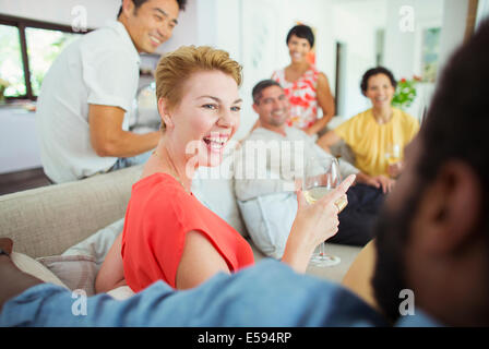 Friends laughing together at party - Stockfoto