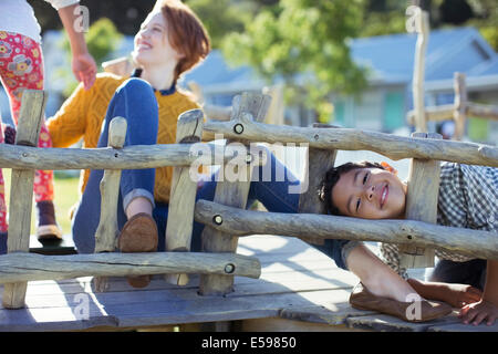 Teacher and students playing on play structure - Stock Photo