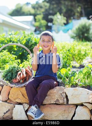 Junge mit Korb von Produkten im Garten - Stockfoto