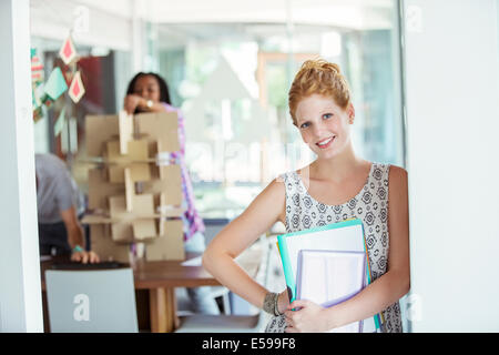 Businesswoman carrying binders in office - Stock Photo