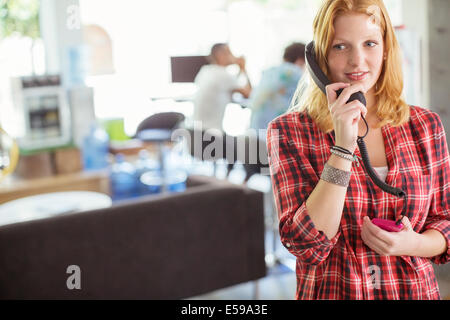 Woman talking on phone in office - Stock Photo