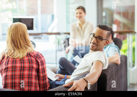 People smiling in office lobby area - Stock Photo