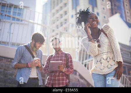 Friends relaxing together on city street - Stock Photo