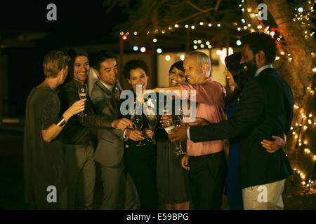 Friends celebrating with champagne at party - Stock Photo