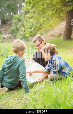 Students and teacher reading map in field - Stockfoto