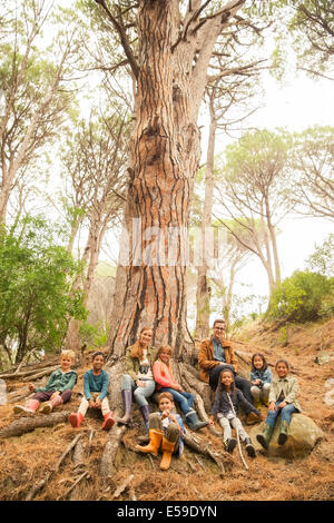 Students and teachers sitting on tree in forest - Stockfoto