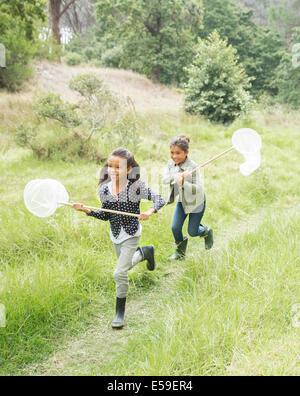 Girls using butterfly nets in field - Stock Photo