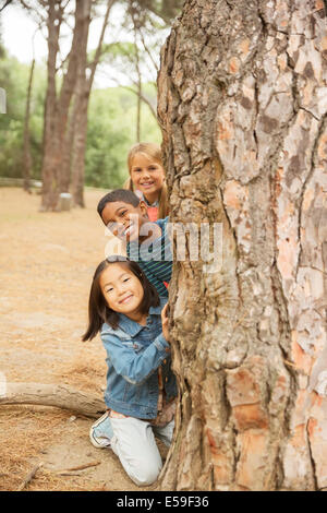 Children peeking out from behind tree in forest - Stockfoto