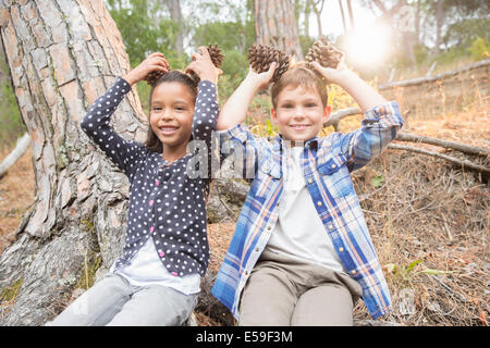 Children playing with pine cones in forest - Stock Photo
