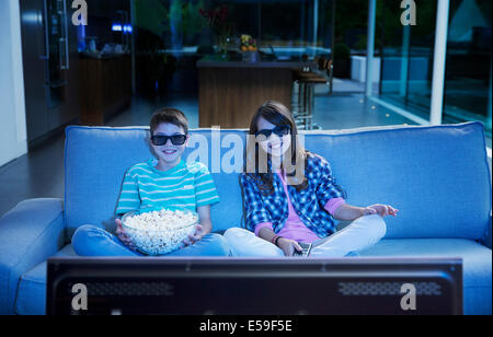 Children watching 3D television in living room - Stock Photo