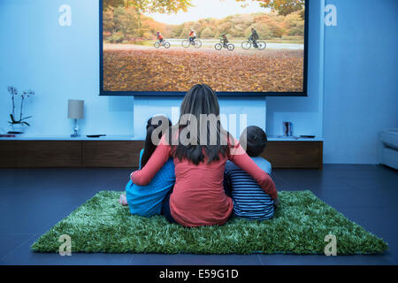 Mother and children watching television in living room - Stock Photo