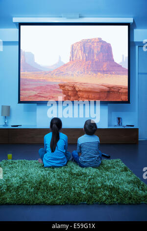 Children watching television in living room - Stock Photo