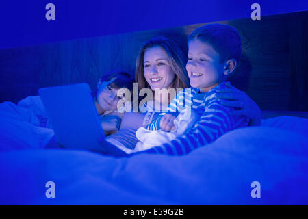 Mother and children using digital tablet in bed - Stock Photo