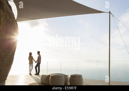 Couple standing on modern balcony - Stock Photo