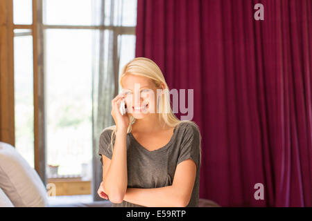 Woman talking on cell phone in bedroom - Stock Photo