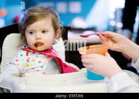 Girl feeding baby girl in high chair - Stock Photo