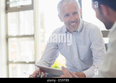 Businessmen laughing together in office - Stock Photo