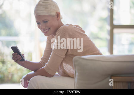 Woman using cell phone on sofa - Stock Photo